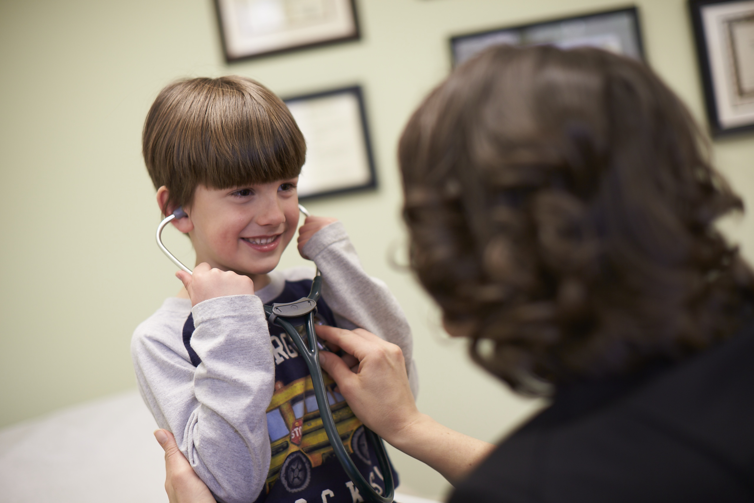 Doctor Samantha Eagle lets a boy listen to his heartbeat through a stethoscope.
