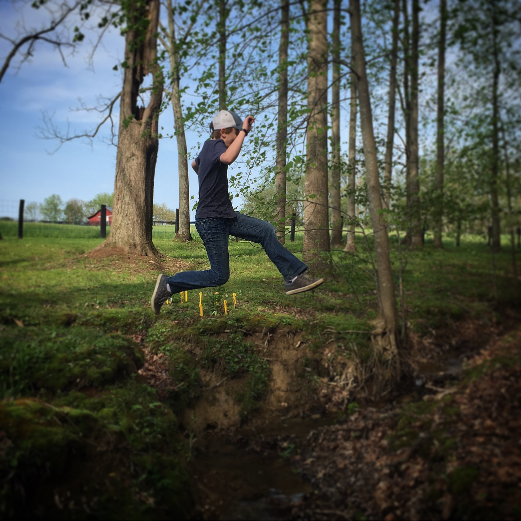 Boy jumping over a creek.