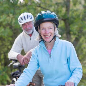 A healthy mature couple getting ready to ride bikes.