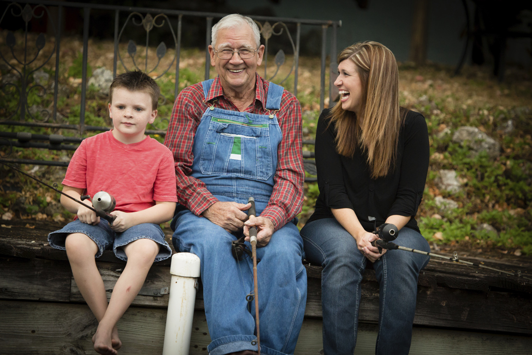 Three generations of a happy family. Smiling grandfather is sitting in between his grandson and his daughter, who is laughing.